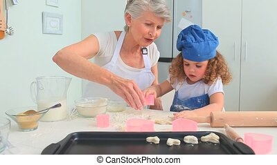 Girl baking with her grandmother in the kitchen