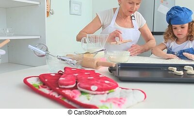 Grandmother and her grand daughter baking together in the...