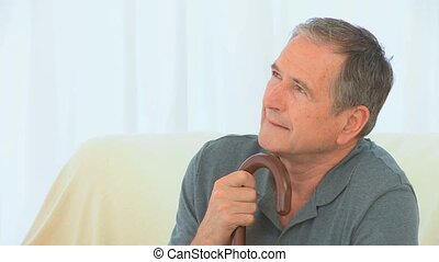 Elderly man thinking on his couch