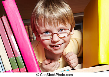Boy in library - Portrait of clever boy looking from between...