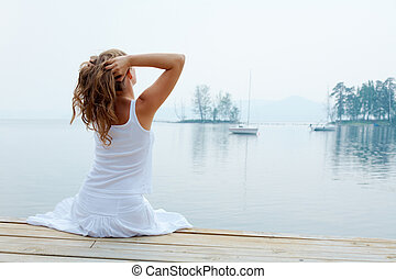 Relaxing by water - Rear view of pretty young lady in white...