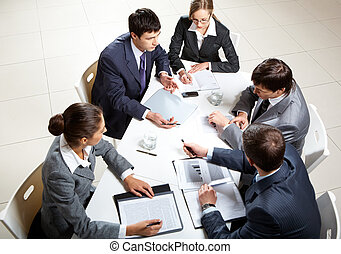 Business briefing - Team of five business people discussing...