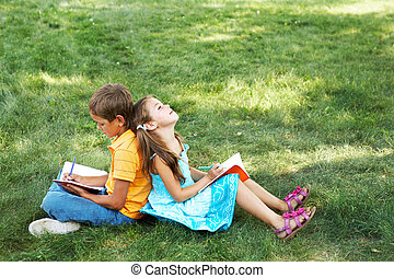 Friends at leisure - Portrait of cute kids seated on green...