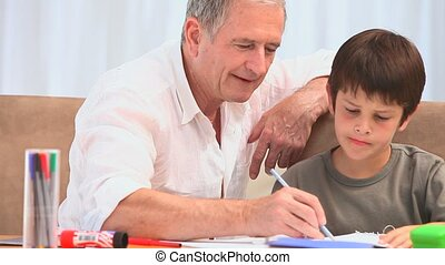 A grandfather helping his grandson to do his homeworks in...