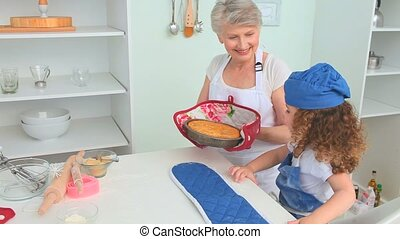 Grandmother with her grand daughter smelling a cake that...