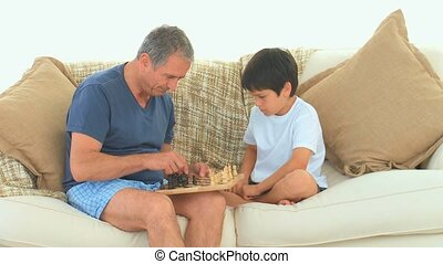 A man playing chess with his grandson