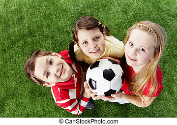 Leisure - Image of happy friends on the grass with ball...