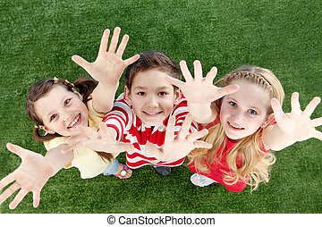 Happy kids - Image of happy friends on the grass raising...