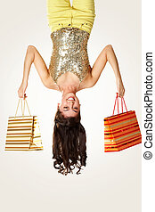 Happy shopper - Upside down view of young girl with...