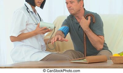 Asian nurse taking the blood pressure of her patient