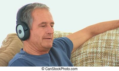 Casual man listening to music with headphones in his couch