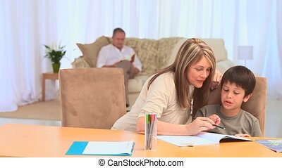 Grandmother helping her grandson to do his homeworks in the...