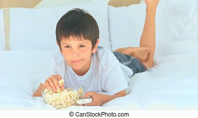 A little boy eating popcorn in front of the tv in the...