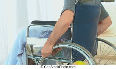 Man in a wheelchair thinking at home