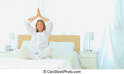 Mature woman doing yogo on her bed