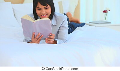 Asian woman reading a book on her bed
