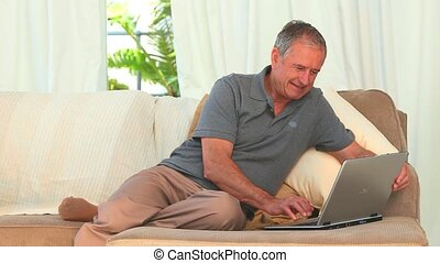 Senior man using a laptop in the living room