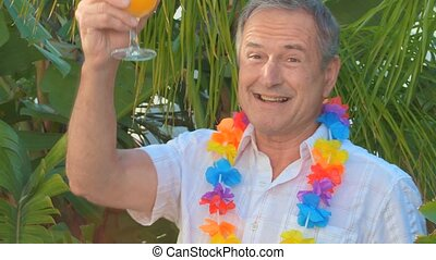 Elderly man with a cocktail during holidays