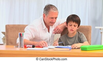 A man hepling his grandson to do his homeworks in the living...