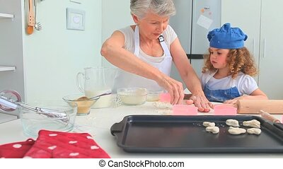 Grandmother teaching how to bake to her grand daughter in...