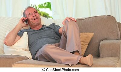 Retired man taking a phone call in his sofa
