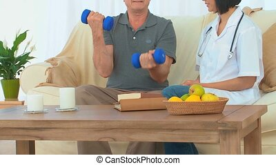 A patient using dumbbells next to his nurse