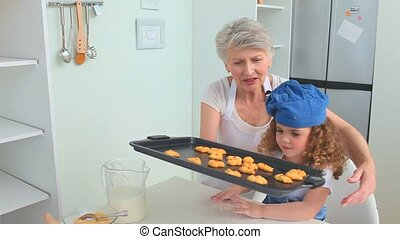 Grandmother and her grand daughter trying cookies that they...