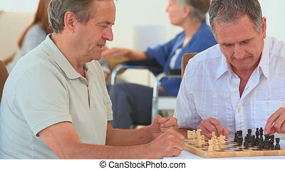 Senior friends playing chess while their wives are talking