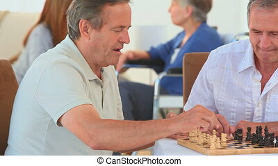 Friends concentrating on a chess game in a nursing home