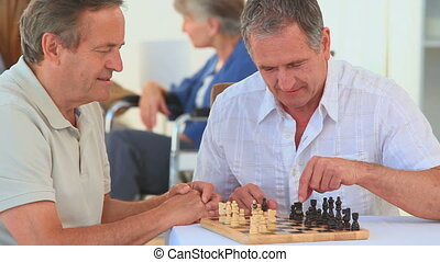 Elderly friends playing chess in a nursing home