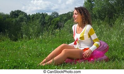 young happy beautiful woman sitting on inflatable seat outdoors