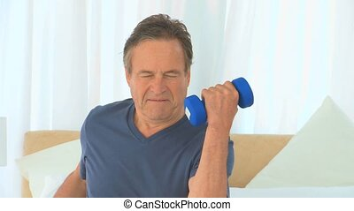 Active man doing exercise with dumbbells in a bedroom