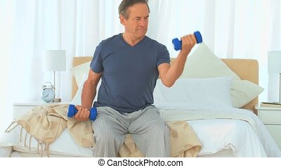 Eldery man doing work out with dumbbells at home