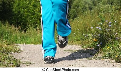 Close up of feet of girl who are carrying out exercises on road in park