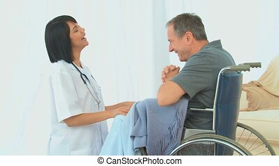 A man in wheelchair talking with his nurse in the living...
