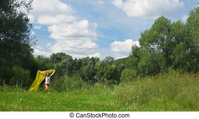 young beautiful woman with yellow silk running in summer park to camera