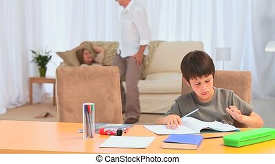 Adorable little boy doing his homeworks in the living room