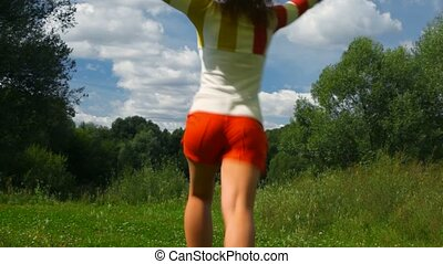 young beautiful woman with yellow silk running in summer park from camera