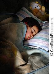 Kid sleeping in dark room with teddy bear