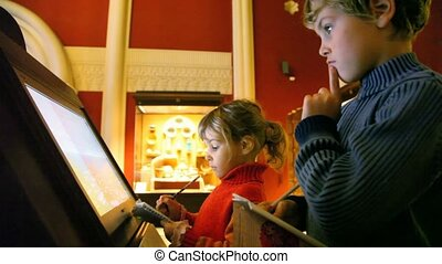 girl and boy looks at interactive display in museum