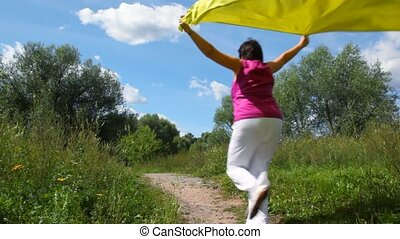 woman with yellow silk running in summer park from camera