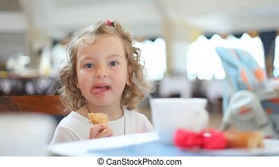 cute little girl eating chocolate ice cream in cafe, tight dof