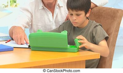 A grandfather looking at his grandson colouring in the...