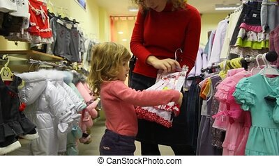 mother with her little daughter buying childrens clothes