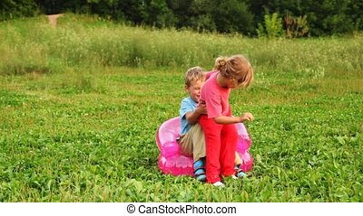 boy and girl play the fool sitting on an children's inflatable armchair on field in park