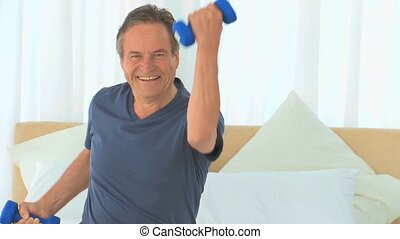 Dynamic man using dumbbells in his bedroom
