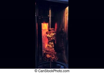 doner meat being roasted in a oven with dark background