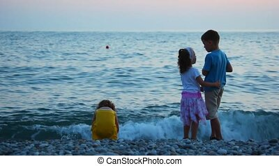 kids throwing pebbles to sea, standing in pebble beach