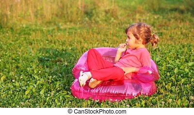 girl sit in childrens inflatable armchair in park and gnaws...
