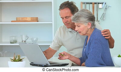 Elderly couple paying something on internet in the kitchen